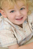 Cheeky Grin Too. A young blond boy dressed laying down and giving a cheeky grin stock photos