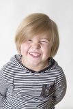 Cheeky grin. Young boy wearing striped shirt and hood smiling at the camera Stock Photography