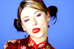 Cheeky lady. In chinese costume with blue background royalty free stock photography