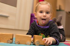 Cheeky little girl is playing with a wooden toy Stock Image
