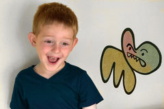 Cheeky monkey. Young boy making silly faces Stock Photography