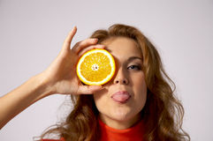Cheeky and playful. A young woman covers one eye with an orange slice and sticks her tongue out cheekily Stock Photos