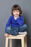 Cheeky preschool child sitting, relaxing with crossed legs. Kid wellbeing concept - cheeky preschool child sitting in relaxing crossed legs position expressing royalty free stock photo