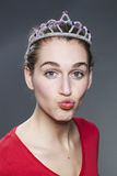 Cheeky 20s girl posing with a tiara on her head and making a pout for love Royalty Free Stock Image