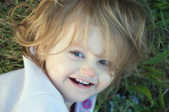 Cheeky toddler. Candid portrait of a cheeky toddle with wild hair rolling on the grass stock images