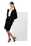 Cheeky woman in a skirt suit. With a blank board ready for text royalty free stock photography