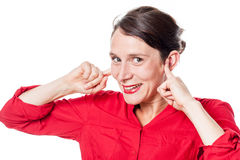 Cheeky young woman smiling in plugging fingers in ears Royalty Free Stock Photos