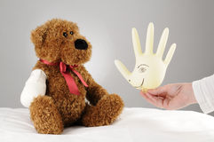 Cheer up teddy. A pediatrician trying to cheer up an injured teddy bear a hospital balloon stock photo