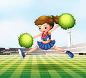 A cheerdancer with green pompoms at the soccer field Royalty Free Stock Photos