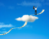 Cheered businessman standing on growing money trend through cloud. With blue sky background royalty free stock images