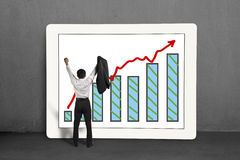 Cheered businessman standing with growth trend and chart on scre Stock Photo