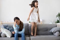 Tired mother has headache little daughter jumping on couch. Cheerful active daughter have fun jumping on sofa. Tired single frustrated women holds her head royalty free stock photos