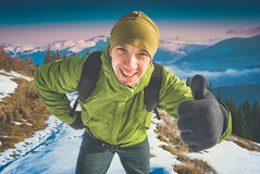 Cheerful active hiker. Instagram stylisation. Cheerful active hiker with backpack showing thumbs up, everything is OK and good. Majestic mountain valley covered Royalty Free Stock Image
