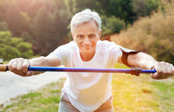 Cheerful active man exercising with a walking pole. Useful sports equipment. Cheerful active aged man leaning forwards and smiling while exercising with a Stock Images