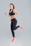 Cheerful active young sportswoman in fitness wear running. Isolated over grey background Stock Images