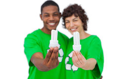 Cheerful activists holding energy saving light bulbs Stock Images