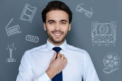 Cheerful actor touching his tie and feeling confident. Famous actor. Positive popular actor feeling good and looking handsome while touching his tie and getting Royalty Free Stock Image