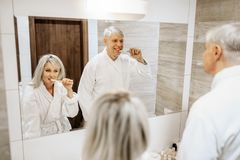 Cheerful adult couple brush teeth in the bathroom. Cheerful adult couple brush teeth at the mirror in the bathroom. Grey-haired mature men and women in bathrobes stock image
