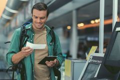 Cheerful adult guy is holding his flight tickets Stock Image