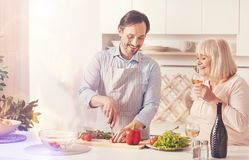 Cheerful adult man cooking with his aged mother. Family love. Cheeful adult men cutting vegetables and making salad while standing in the kitchen with his aged Stock Photo