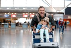 Cheerful adult man and little girl are playing in terminal stock photography