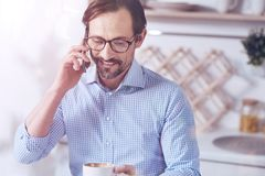 Cheerful adult man talking on smart phone Stock Photography