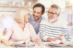 Cheerful adult son embracing his parents. True feelings. Cheerful adult men smiling and embracing his aged parents while sitting together in the kitchen Stock Photography