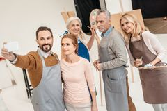 cheerful adult students of art class taking selfie stock images