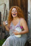 Cheerful adult woman drinking milk in the village outside Royalty Free Stock Image