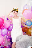 Cheerful adult woman tries on toy crown Royalty Free Stock Photos