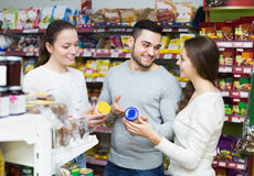 Cheerful adults choosing tinned food Royalty Free Stock Photos