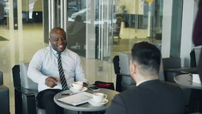 Successful African American businessman in formal clothes smiling and discussing financial report with his Caucasian stock video footage