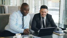 Cheerful African American businessman in formal clothes discussing business project with his caucasian colleague on his. Laptop in stylish cafe during lunch stock video
