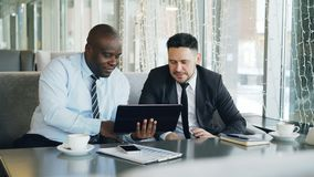 Cheerful African American businessman in formal clothes using digital tablet discussing startup ideas with his caucasian. Partner in stylish cafe indoors during stock footage