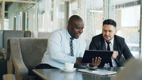 Cheerful African American businessman in formal clothes using digital tablet discussing startup project with his. Caucasian partner in stylish cafe indoors stock footage