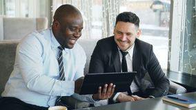 Cheerful African American businessman in formal clothes using digital tablet discussing startup project with his. Caucasian partner in stylish cafe indoors stock video footage