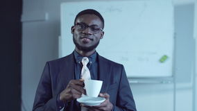 Cheerful african american businessman having a hot drink stock footage