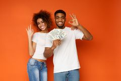 Cheerful african-american couple showing ok signs with bunch of money royalty free stock photos