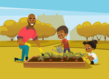 Cheerful African American father and two kids dressed in rubber boots cultivate vegetables growing in bed against trees. On background. Concept of family Stock Images