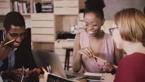 Cheerful African American female manager brainstorming with happy multiethnic colleagues in modern loft healthy office.