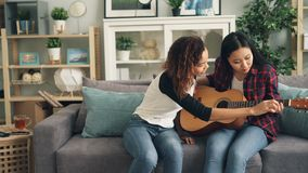 Cheerful African-American girl is teaching her Asian friend to play the guitar at home. Young women are sitting on sofa stock video