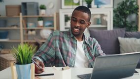 Cheerful African American guy distant worker is working at home using laptop sitting at desk in studio looking at screen