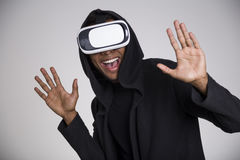 Cheerful African American guy in vr glasses. Close up of an African American youth playing a virtual reality game. His hands are in the air. He is wearing a Stock Image