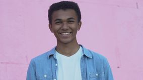 Cheerful African-American male teenager smiling at camera, positive mood