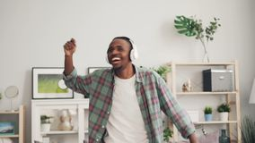 Cheerful African American man is dancing and laughing listening to music with headphones enjoying free time at home in stock video footage