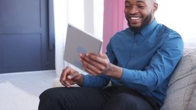 Cheerful man using digital tablet on sofa stock footage