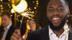 Cheerful african-american man holding bengal light at party celebrating new year stock footage