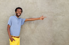 Cheerful african american man pointing to wall Royalty Free Stock Photos