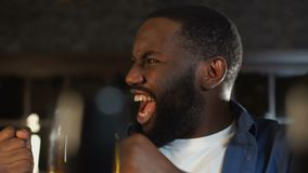 Cheerful african american man rejoicing victory of sports team sitting in pub stock video