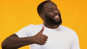 Cheerful African-American man showing thumbs up isolated on yellow background stock footage